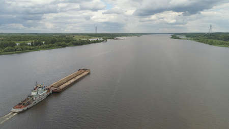 Aerial view:Barge with cargo on the river Volga. River tugboat moves cargo barge, Cargo ship on the river. Banque d'images