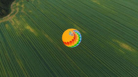 Aerial view Hot air balloon in the sky over a field in the countryside in the beautiful sky and sunset. Balloon silhouette with sunrise, Aerostat fly in the countryside. Stock Photo