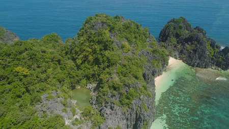 Aerial view Matukad island with sand beach and turquoise water in blue lagoon among coral reefs, Caramoan Islands, Philippines. Landscape with sea, tropical beach.