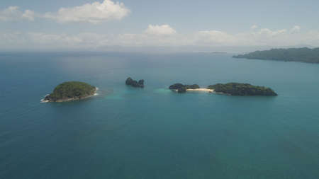 Aerial view islands with sand beach Lahus and turquoise water in blue lagoon among coral reefs, Caramoan Islands, Philippines. Landscape with sea, tropical beach.