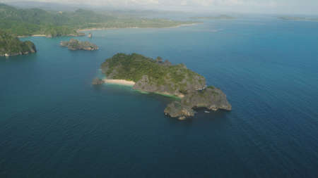 Aerial view of Groups islands with sand beach and turquoise water in blue lagoon among coral reefs, Caramoan Islands, Philippines. Mountains covered with tropical forest. Stock Photo