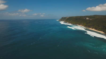 Aerial view of tropical beach with large wave. Large waves of turquoise water crushing on a beach Melasti, Bali,Indonesia. Travel concept. Фото со стока