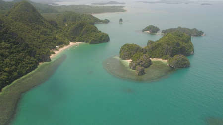 Aerial view of island Kagbalinad with sand beach and turquoise water in blue lagoon among coral reefs, Caramoan Islands, Philippines. Mountains covered with tropical forest.