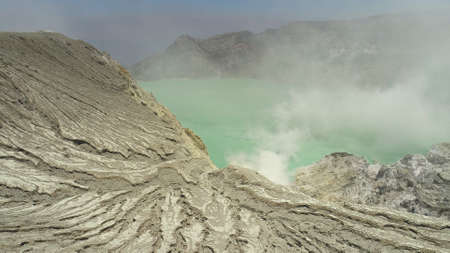 Aerial view mountain landscape with crater acid lake Kawah Ijen where sulfur is mined. Sulfur gas, smoke. Ijen volcano complex group of stratovolcanoes in East Java Indonesia