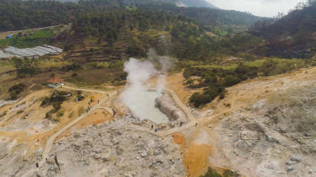 plateau with volcanic activity, mud volcano Kawah Sikidang, geothermal activity and geysers. aerial view volcanic landscape Dieng Plateau, Indonesia. Famous tourist destination of Sikidang Crater it still generates thick sulfur fumes. Banco de Imagens - 113331138