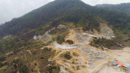 plateau with volcanic activity, mud volcano Kawah Sikidang, geothermal activity and geysers. aerial view volcanic landscape Dieng Plateau, Indonesia. Famous tourist destination of Sikidang Crater it still generates thick sulfur fumes.