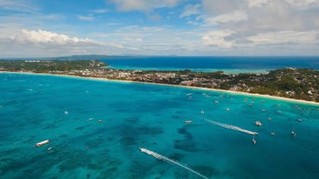 Aerial view of beautiful tropical island with white sand beach, Boracay, hotels and tourists. Tropical lagoon with turquoise water and white sand. Beautiful sky, sea, beach, resort. Seascape: Ocean and beautiful beach paradise.. Stock Photo