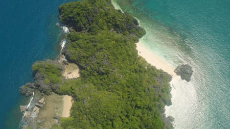 Aerial view Matukad island with sand beach and turquoise water in lagoon among coral reefs, Caramoan Islands, Philippines. Landscape with sea, tropical beach. Stock Photo