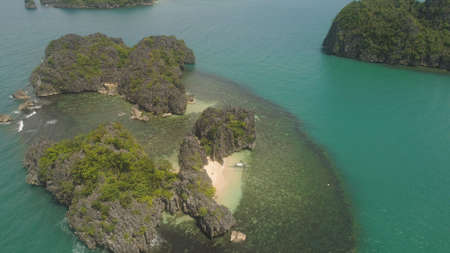 Aerial view Minalahos island with sand beach and turquoise water in lagoon among coral reefs, Caramoan Islands, Philippines. Landscape with sea, tropical beach. Stock Photo
