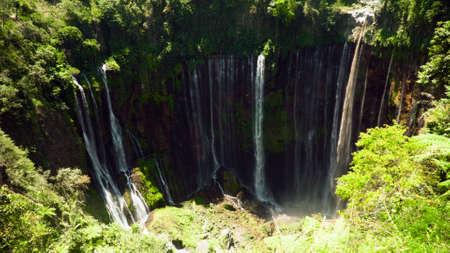 waterfall Coban Sewu in tropical forest, Java Indonesia. tumpak sewu waterfall in rainforest aerial footage Imagens
