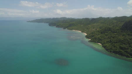 Aerial view coastline with beach and mountains covered with tropical forest in province Caramoan, Philippines. Landscape with sea, mountains and beach.