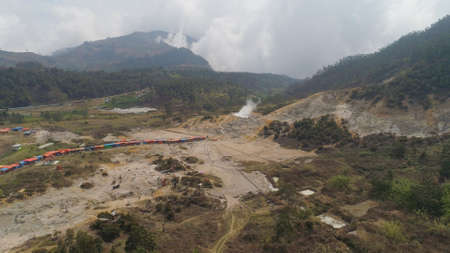 plateau with volcanic activity, mud volcano Kawah Sikidang, geothermal activity and geysers. aerial view volcanic landscape Dieng Plateau, Indonesia. Famous tourist destination of Sikidang Crater it still generates thick sulfur fumes. Banco de Imagens - 115249293