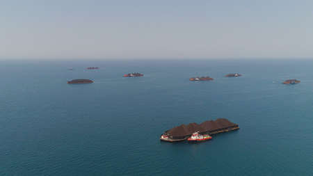 aerial view barges full coal anchored at sea near coal fired power station waiting be transported. coal barges and tugboats java, paiton indonesia 免版税图像