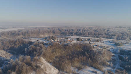aerial view village among the fields and forests in winter. winter landscape snow covered field and trees in countryside. Stock fotó