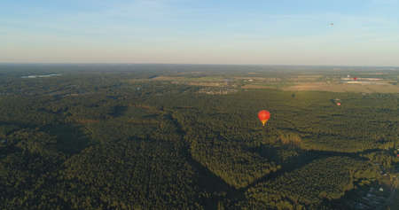 Aerial view Hot air balloons in sky over fields in countryside, beautiful sky and sunset. Aerostat fly over countryside.