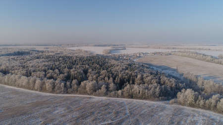 aerial view winter landscape snow covered field and trees in countryside. winter in countryside. Snow covered farmland and trees during winter