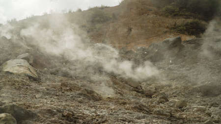 plateau with geothermal volcanic activity, geysers. volcanic landscape Dieng Plateau, Indonesia. Famous tourist destination of Sikidang Crater it still generates thick sulfur fumes.