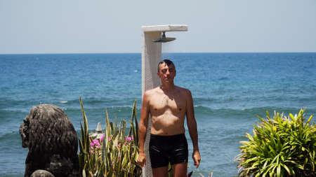 Man takes shower on his body on beach shower against sea. Beach shower along ocean, travel concept Standard-Bild - 115257397