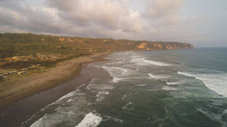 sandy beach parangtritis near ocean with big waves, people in tropical resort at sunset. Yogyakarta, Indonesia. aerial view seascape, ocean and beautiful beach. Travel concept. Indonesia, jawa Standard-Bild - 115258478
