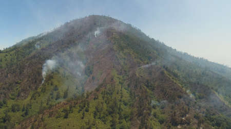 aerial view forest fire smoke on slopes hills. wild fire in tropical forest, Java Indonesia. natural disaster fire in Southeast Asia Standard-Bild - 115258502