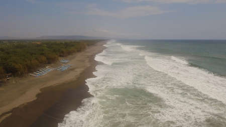 aerial view sandy beach near ocean with big waves at sunset time in tropical resort, Yogyakarta, Indonesia. seascape, ocean and beautiful beach. Travel concept. Indonesia, java Standard-Bild - 115258504