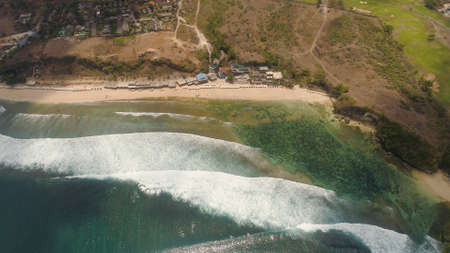 Aerial view rocky seashore with sandy beach. seascape ocean surf and tropical beach large waves turquoise water crushing on beach Bali,Indonesia. Travel concept. Standard-Bild - 115258600