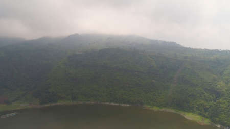 Aerial view lake Menjer in fog and clouds. lake in mountains with green rain forest. Tropical landscape with forest and lake. Java Indonesia Standard-Bild - 115258605