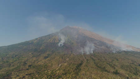 slopes volcano with forest fire, farmland at foot of the volcano Agung. tropical landscape aerial view mountains are covered with forest. Bali, Indonesia. Standard-Bild - 115259689