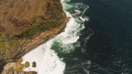 aerial view rocky coastline with cliffs, ocean surf with breaking waves in coast. seascape waves break on rocky shore java, indonesia Standard-Bild - 115259692