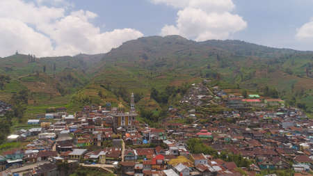 asian town with mosque in mountains among agricultural land, rice terraces. mountains with farmlands, rice fields, village, fields with crops, trees. Aerial view farm lands on mountainside. tropical landscape Java Indonesia. Standard-Bild - 115259696