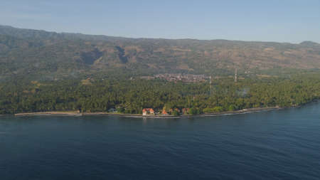 aerial seascape coastline with black sand beach, palm trees, hotel, mountains in tropical resort. Bali,Indonesia, travel concept. Standard-Bild - 115259699