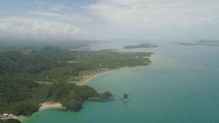Aerial view of islands with sand beach and turquoise water in lagoon among coral reefs, Caramoan Islands, Philippines. Mountains covered with tropical forest.