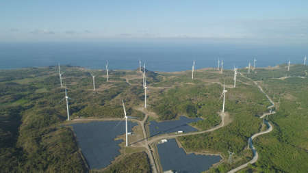 Aerial view of Windmills for electric power production on the seashore. Bangui Windmills in Ilocos Norte, Philippines. Solar farm, Solar power station. Ecological landscape: Windmills, sea, mountains. Pagudpud.