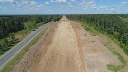 Construction of toll roads in rural areas. Aerial view construction of a new highway next to the old highway.