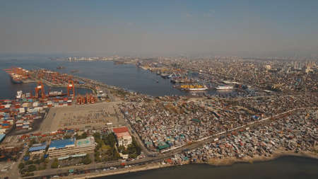 Aerial view industrial cargo port with ships and cranes. View of the cargo port and container terminal. Container cranes in Manila Bay. Cargo ship in industrial port. Manila, Philippines. Stockfoto
