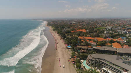 Aerial view sand beach with resting people, hotels and tourists, sun umbrellas, Bali, Kuta. surfers on water surface. Seascape, beach, ocean, sky sea Travel concept