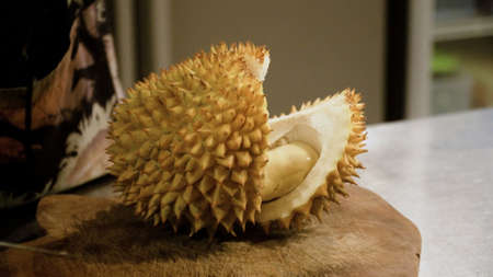 hand peeling and cuts durian fruit. caucasian man peeling durian in kitchen room