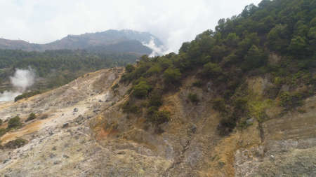 plateau with volcanic activity, geothermal activity and geysers. aerial view volcanic landscape Dieng Plateau, Indonesia. Famous tourist destination of Sikidang Crater it still generates thick sulfur fumes. Banco de Imagens - 117535423