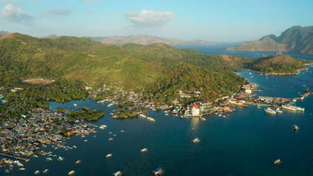 Aerial view Coron city with slums and poor district. sea port, pier, cityscape Coron town with boats on Busuanga island, Philippines, Palawan. Seascape with mountains.