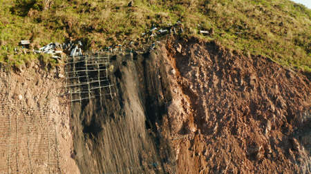 Protection of road from mountain slough, rockfall with metal accumulative restraining net fences. Workers constructing anti-landslide concrete wall prevent protect against rock slides. Rockfall protection. Workers strengthen the slope of the mountain with steel grid preventing rockfall and landslide on the road.