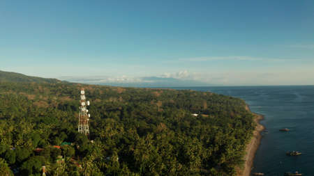 Antennas and microwaves link dishes of mobile phone network and TV transmitter on telecommunication towers aerial view. Camiguin, Philippines