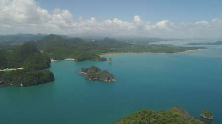 Aerial view of Groups islands with sand beach and turquoise water in blue lagoon among coral reefs, Caramoan Islands, Philippines.