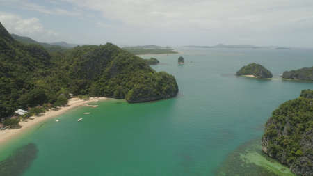 Aerial view islands with sand beach and turquoise water in blue lagoon among coral reefs, Caramoan Islands, Philippines. Landscape with sea, tropical beach. Stock Photo