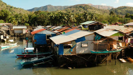 Coron city with slums and poor district. Old wooden house standing on the sea in the fishing village. Houses of local poor people.Busuanga, Coron, Philippines. houses community standing in water in fishing village.