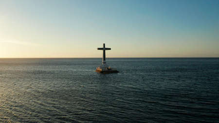 Catholic cross in sunken cemetery in the sea at sunset, aerial view. Sunset at Sunken Cemetery Camiguin Island Philippines.