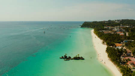 White sand beach and Willys rock with tourists and hotels and sailing boat on Boracay Island. Aerial drone: Tropical white beach with sailing boat. Summer and travel vacation concept.