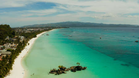 White sand beach and Willys rock with tourists and hotels and sailing boat, aerial view. Boracay, Philippines. Summer and travel vacation concept.