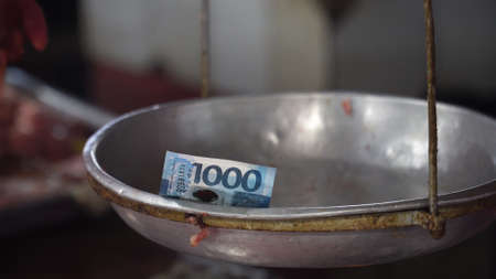 Money on the weighing scales in the street market. 1000 Philippine Pesos on an old scale. Shopping concept. 写真素材