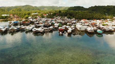 Old wooden house standing on the sea in the fishing village, aerial view. Dapa, Siargao, Philippines. Stock Photo