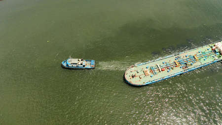 Aerial view of tugboats maneuvers other barges or vessel. Tugs and cargo ship on the river